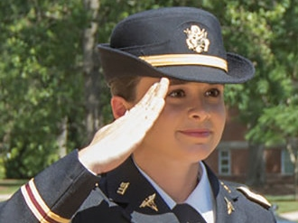 Photo portrait of a female army ROTC nurse saluting an officer who is standing outside the frame of the photo.