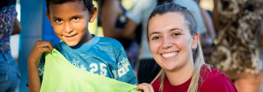 photo of a USC Upstate student in Nicaragua, holding up a South Carolina flag with a little boy