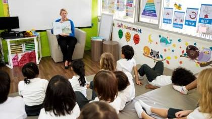 Teacher with book reading to students