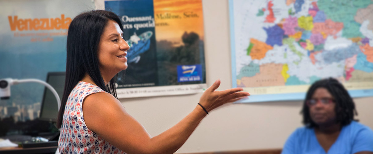 Professor Gaby Drake teaching Spanish course  with students and world map in background