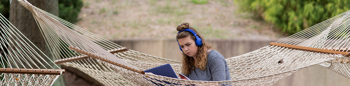 Female student studying in a hammock.